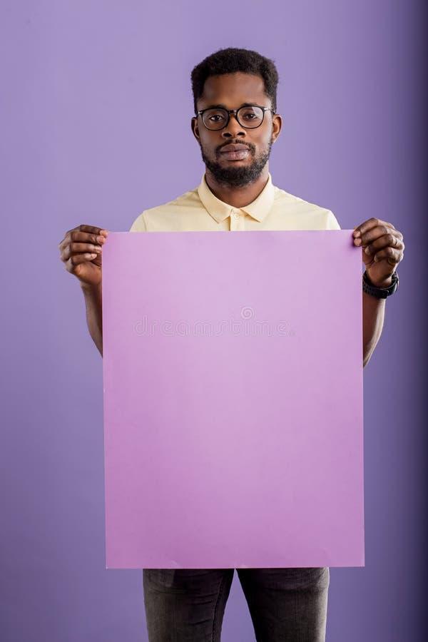 Image du jeune homme d'afro-am?ricain tenant le conseil vide sur le fond violet images stock