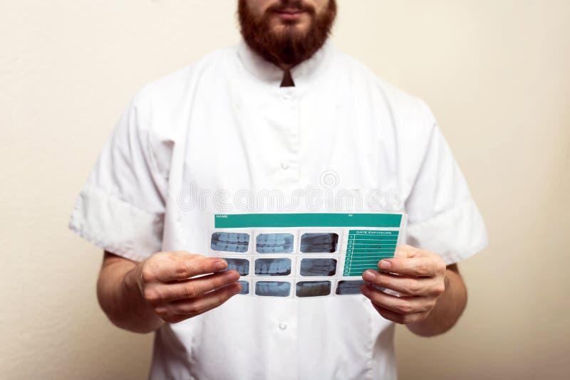 Image du médecin ou du dentiste masculin tenant et regardant le vieux rayon X dentaire, analysant photo stock