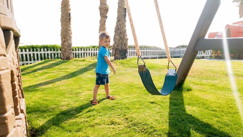 Image du petit garçon mignon d'enfant en bas âge jouant avec des oscillations sur le palyground au parc photos stock