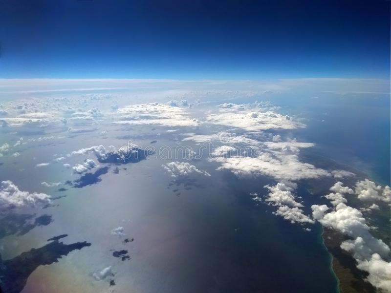 Image of the earth with blue sky and white clouds over the sea with sun reflected on the water and small islands stock photos