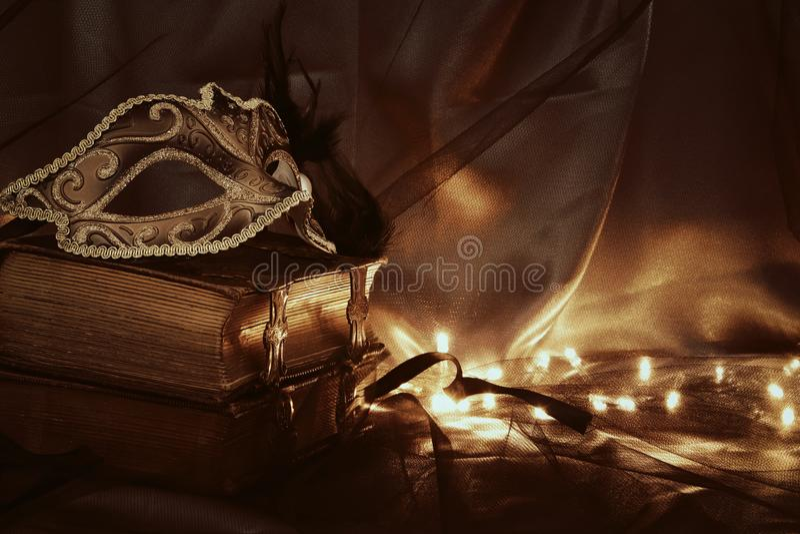 Image of elegant gold and black venetian mask over tulle background. Image of elegant gold and black venetian mask over tulle background royalty free stock photos
