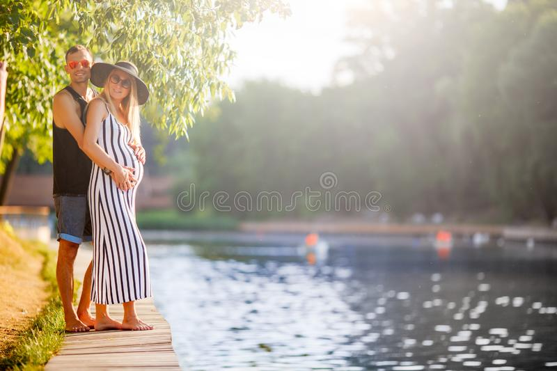 Image of embracing pregnant women and men standing near river on summer day royalty free stock images