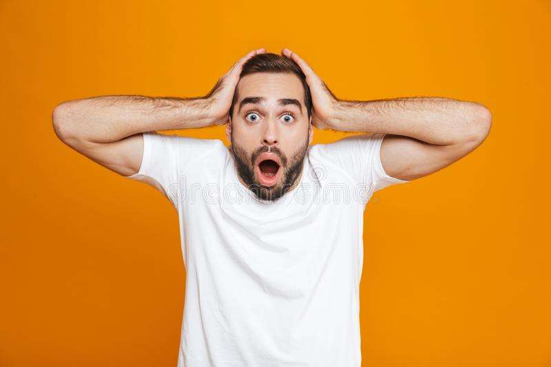 Image of emotional man 30s with beard and mustache grabbing head while standing,  over yellow background stock photos