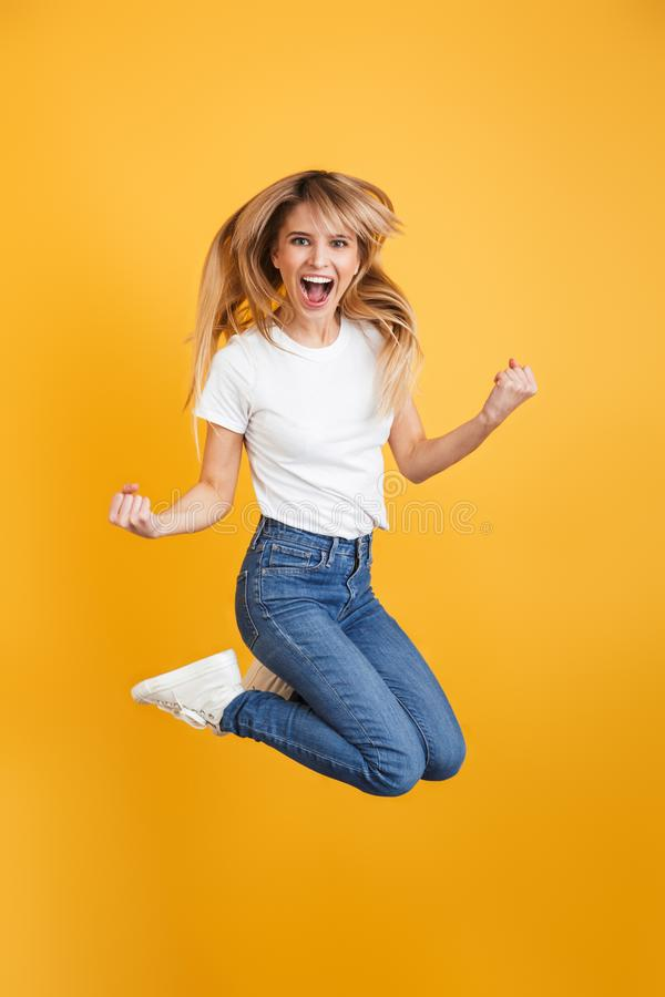 Emotional screaming positive young blonde woman jumping isolated over yellow wall background dressed in white casual t-shirt make. Image of emotional screaming royalty free stock photography