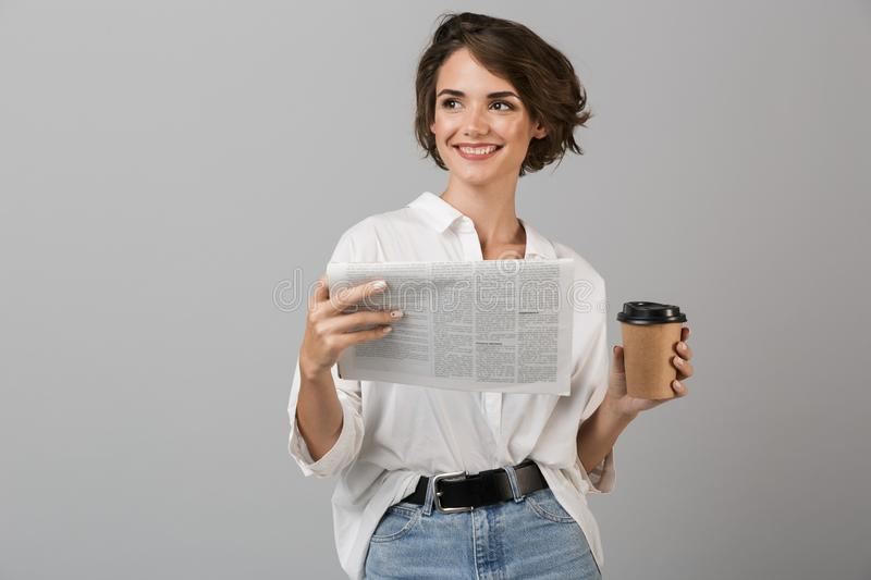 Emotional young business woman posing over grey wall background reading newspaper drinking coffee royalty free stock image