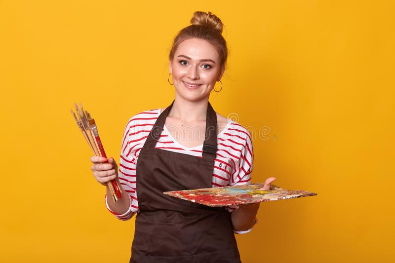 Image of enthusiastic young artist standing  over yellow background, smiling sincerely, holding set of brushes and dirty stock image