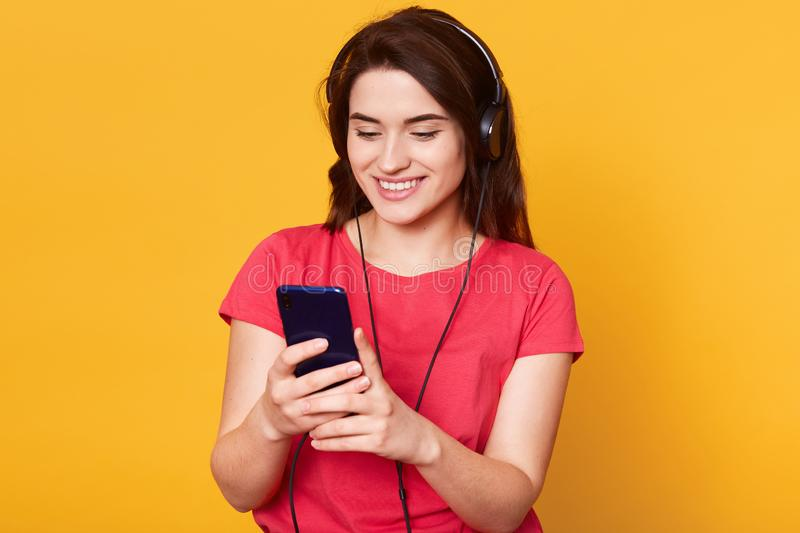 Image of european brunette woman with straight hair, has pleasant appearance, holding cell phone and listening to music via royalty free stock photos