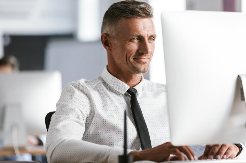 Image of european businesslike man 30s wearing white shirt and t. Ie sitting at desk in office and working at computer royalty free stock photos