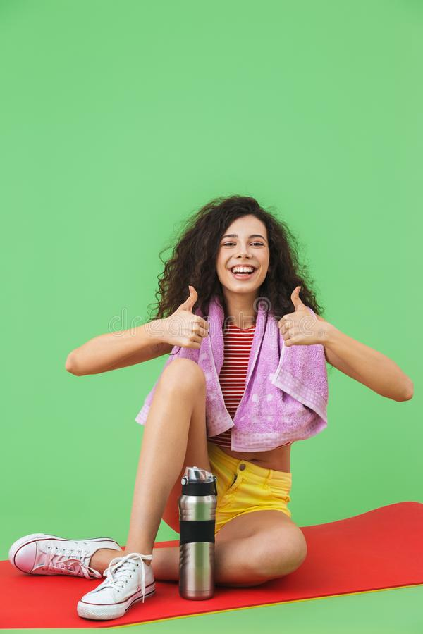 Image of european girl 20s in sportswear with towel over neck resting and sitting on fitness mat after workout royalty free stock photo