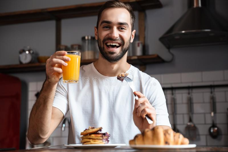 Image of european guy 30s eating food while having breakfast in modern apartment royalty free stock images