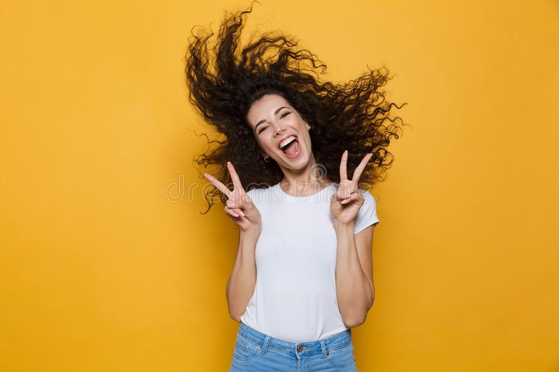 Image of european woman 20s laughing and having fun with shaking. Hair isolated over yellow background royalty free stock photography