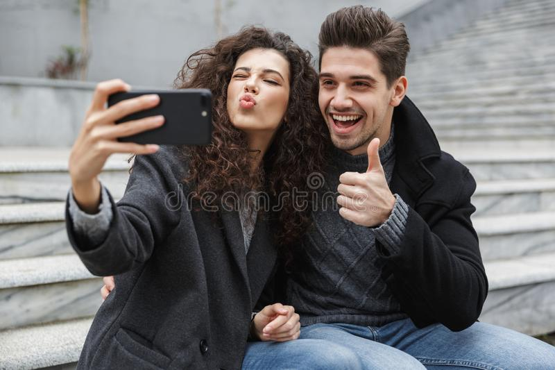 Image of excited couple man and woman 20s in warm clothes, taking selfie photo on cell phone while sitting on stairs outdoor. Image of excited couple man and royalty free stock photos
