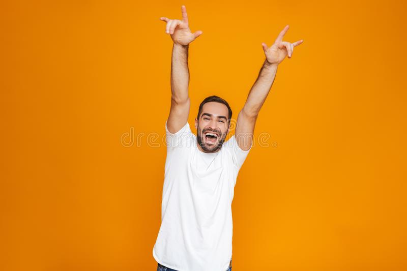 Image of excited guy 30s in t-shirt rejoicing and smiling while standing, isolated over yellow background stock photography