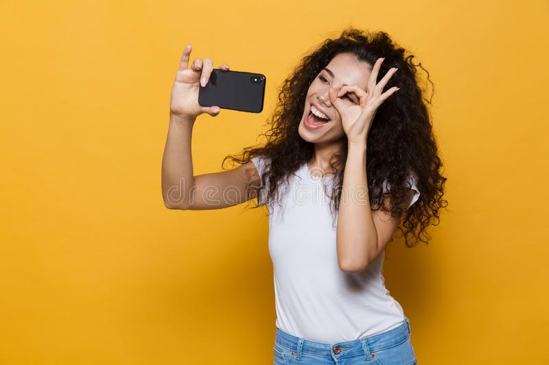 Happy cute young woman posing isolated over yellow background take a selfie by mobile phone. royalty free stock photos
