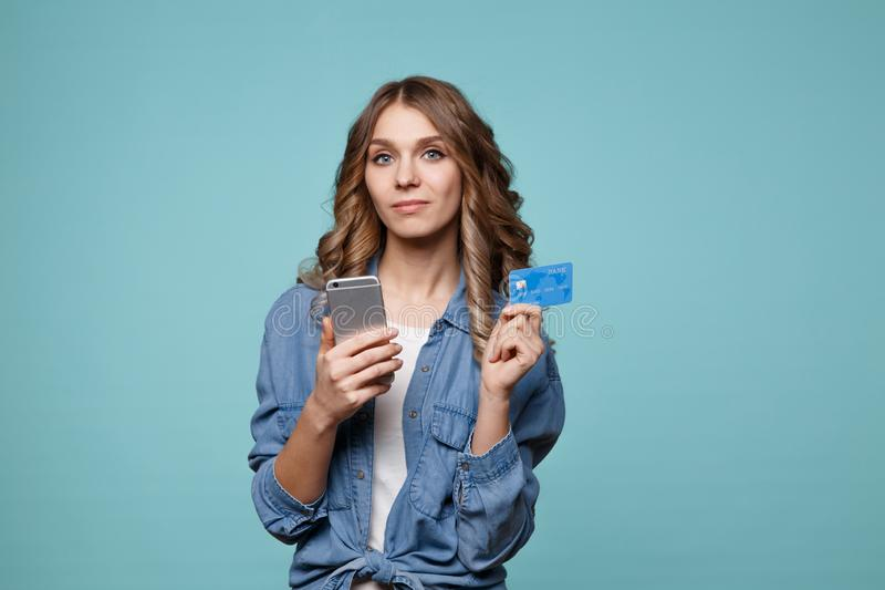 Image of excited young lady isolated over blue background using mobile phone holding credit stock photo
