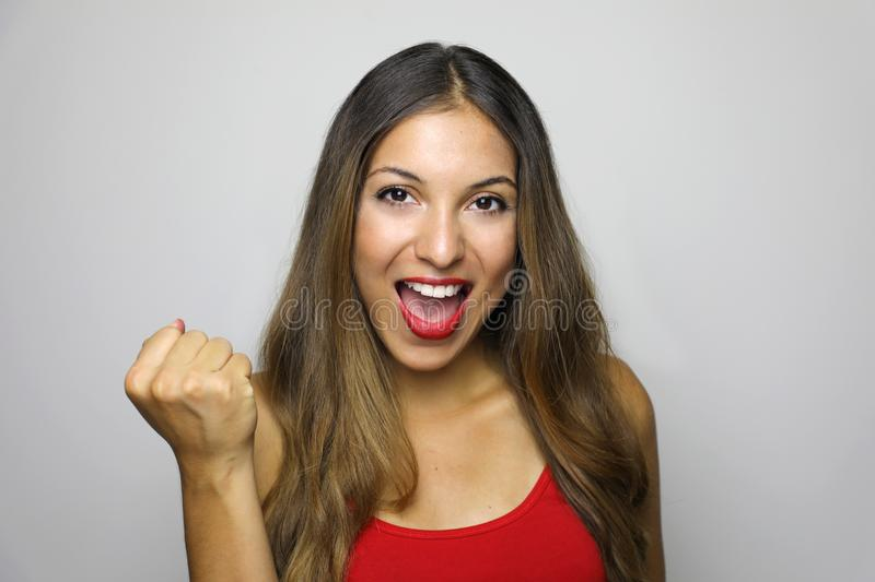 Image of excited young lady with red tank top standing over gray background making winner gesture stock photos