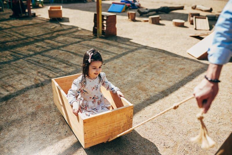 Image extérieure horizontale de la fille heureuse mignonne jouant avec son père Petite fille de papa et d'enfant en bas âge ayant photos stock