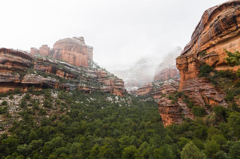 Panoramic photograph of snow covered red rocks at Fay Canyon in Sedona. Arizona. Image facing down Fay Canyon in Sedona, Az with green brush in the foreground royalty free stock photos