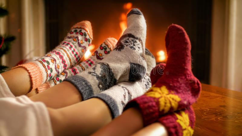 Image of family warming their feet at burning fireplace at living room. Photo of family warming their feet at burning fireplace at living room royalty free stock photo