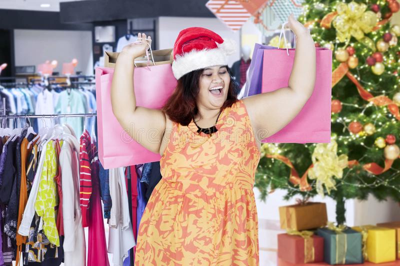 Happy fat woman with Christmas gifts in mall royalty free stock photography