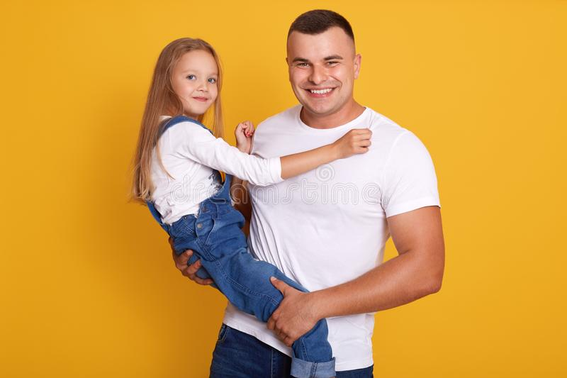 Image of father holding his child, dad and little child looking happily directly at camera, family ering casual clothing, models royalty free stock images