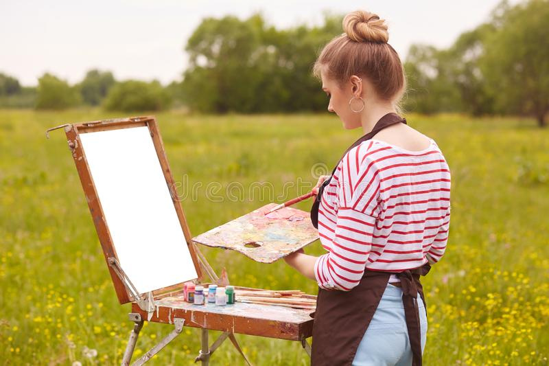 Image of female artist working with watercolor painting, posing in open air, female wearing white casual shirt with red stripes, stock image