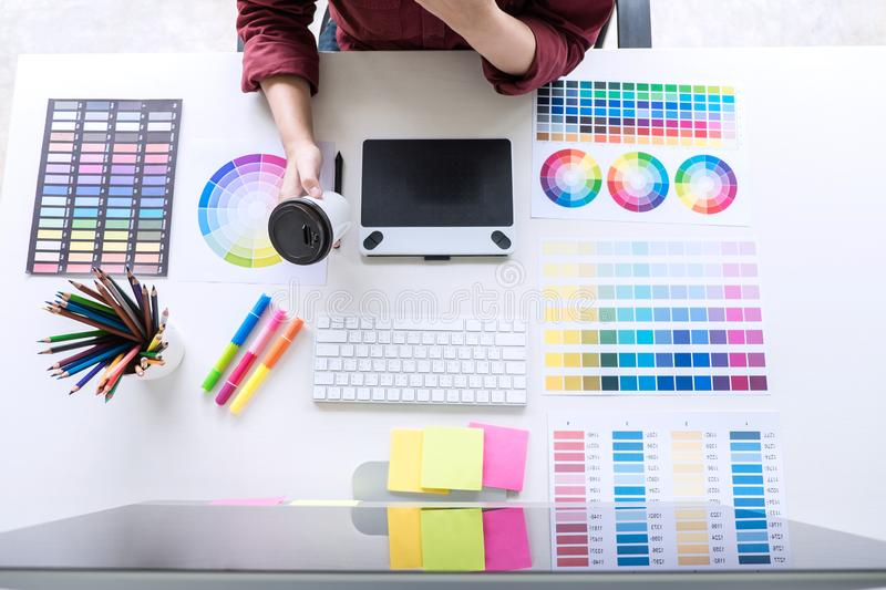 Image of female creative graphic designer working on color selection and drawing on graphics tablet at workplace, top view. Workspace royalty free stock photo