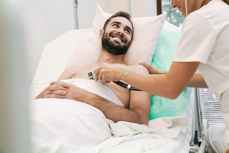Image of female doctor examining young patient man in hospital bed royalty free stock photo
