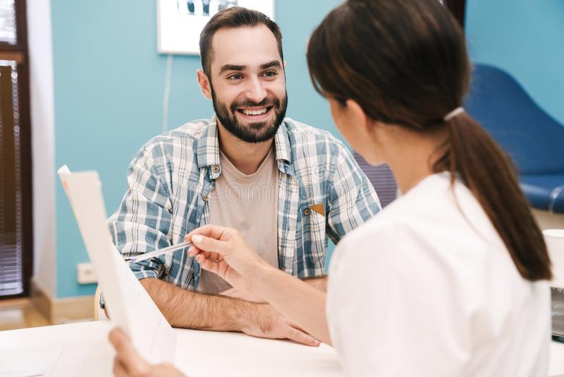 Image of female doctor and patient man looking at health results royalty free stock photography