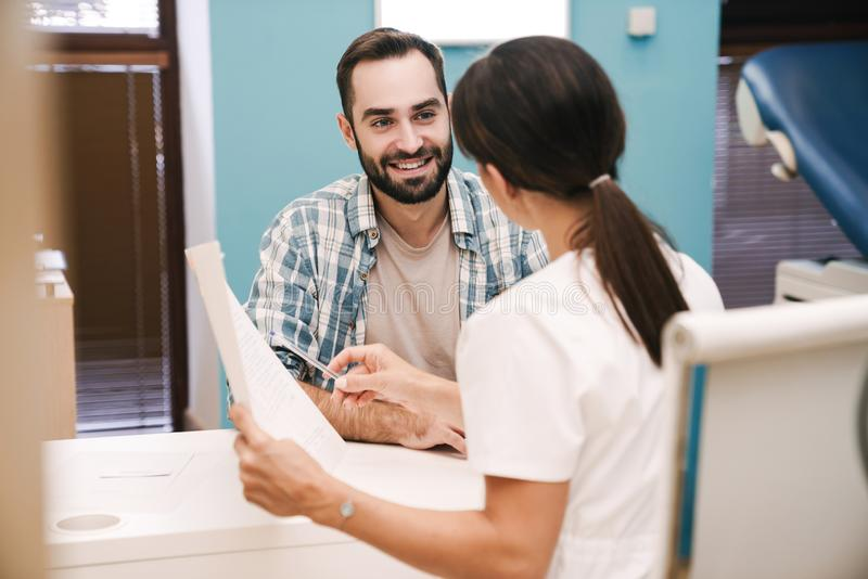 Image of female doctor and patient man looking at health results royalty free stock images