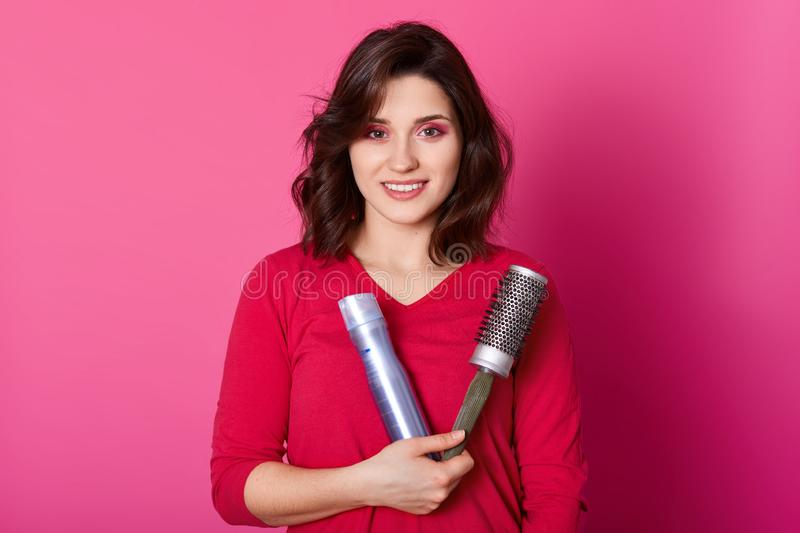 Image of female hairdresser holds comb and hairspay, wears red sweater, ready to make hairstyle her client, models over pink royalty free stock photos