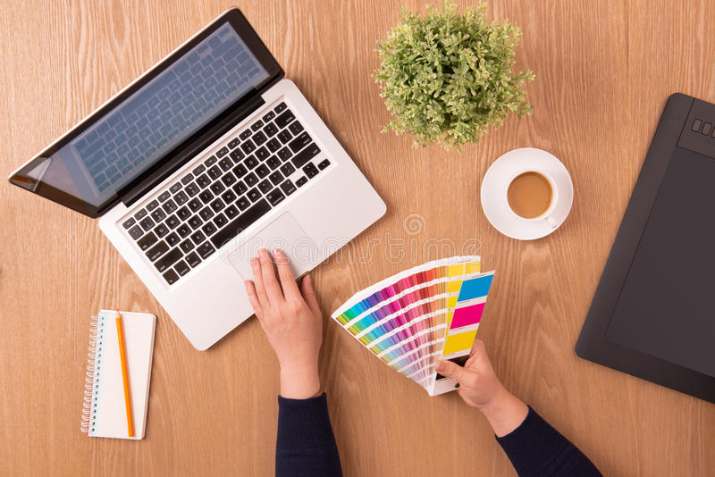 Image of female hands using color swatches for selection. Modern designer workplace. Concept of design working office. Modern workplace office. Top view stock image