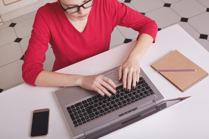 Image of female student in red clothes keyboards on laptop computer, surrounded with mobile phone and notebook, sits at white desk stock photography