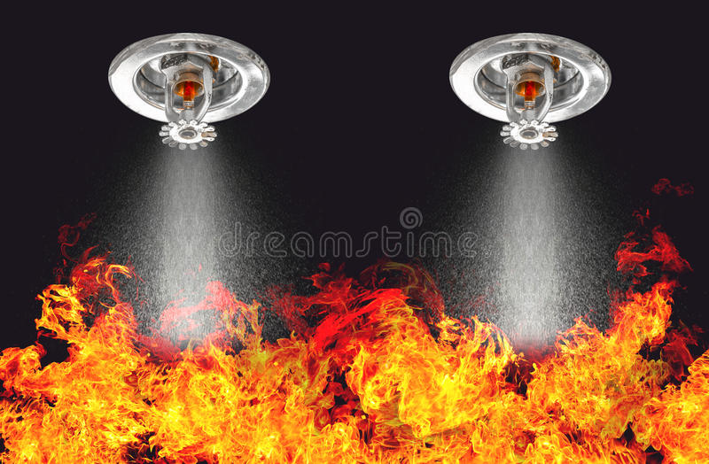 Image of Fire Sprinklers Spraying with fire background. Fire sprinklers are part of an overall safety protocol for fire and life royalty free stock photography