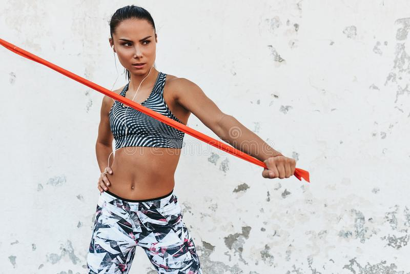 Image of fitness athlete woman standing against concrete wall doing stretching exercises holding a red resistance band. Athletic stock image