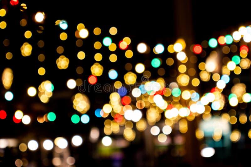 Image floue Des lampes à cordes décoratives extérieures pendent dans le jardin pendant la saison des festivals de nuit photographie stock libre de droits
