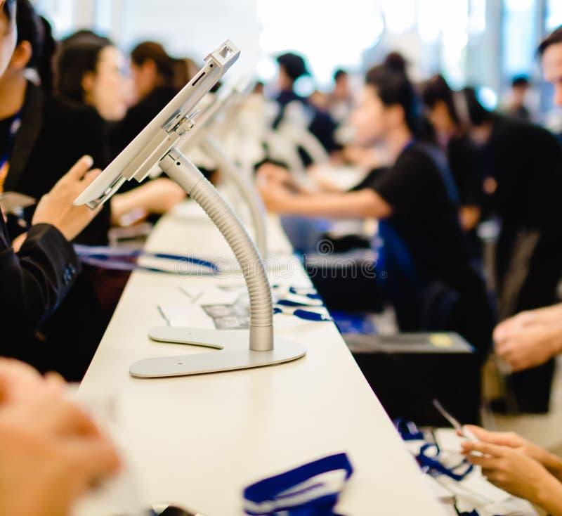 Image floue pour l'arrière-plan de la main et de la tablette pour l'inscription à l'événement séminaire ou réunion avec des perso photo libre de droits