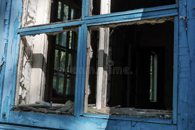 Wooden frames of broken windows in an abandoned house royalty free stock photo