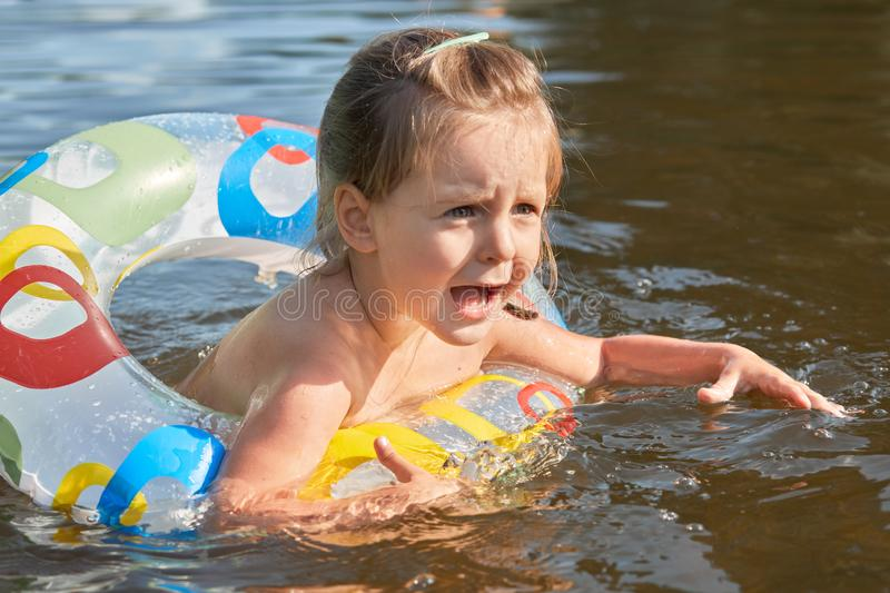 Image of frightened sweet little kid opening mouth and eyes widely with scare, swimming with rubber circle, screaming for help, stock photography