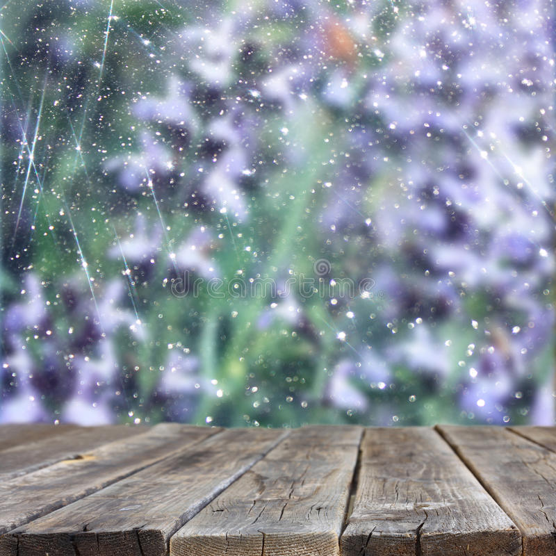 Image of front rustic wood boards and background of beautiful flowers field. bokeh lights overlay.ready for product display stock photo