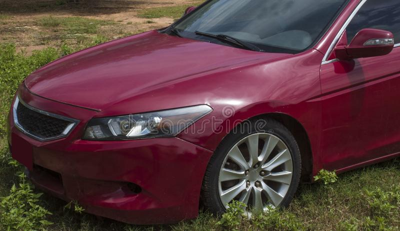 Image of front side of car showing headlights suitable for commercial illustration of used cars concepts. Front side of red cars with no logos in green Field stock photos