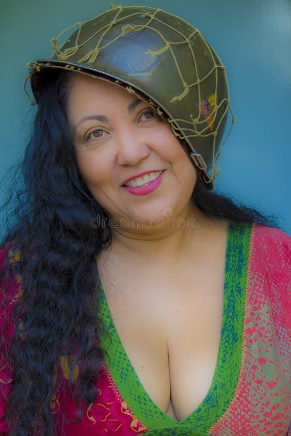 Image gentille d'une femme de sourire avec de longs cheveux noirs utilisant un chemisier rouge et vert avec un casque de soldat images libres de droits