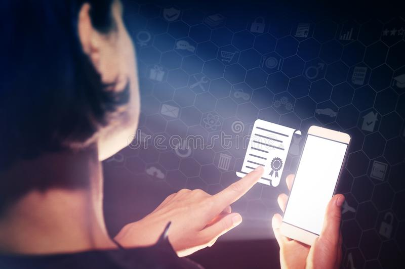 Concept of online education, diploma. Image of a girl with a smartphone in hands. She presses on the certificate diploma icon. Concept of online education royalty free stock image