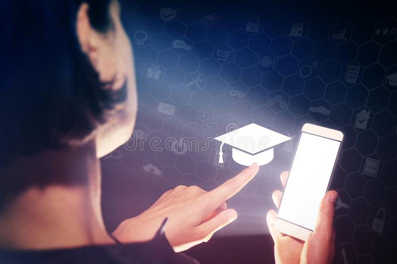 Concept of online education, choose of career. Image of a girl with a smartphone in hands. She presses on the graduation hat cap icon. Concept of online royalty free stock photos
