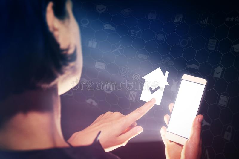 Online buying or rent estate. Image of a girl with a smartphone in hands. She presses on the house icon. Real estate. Online buying or rent estate stock images