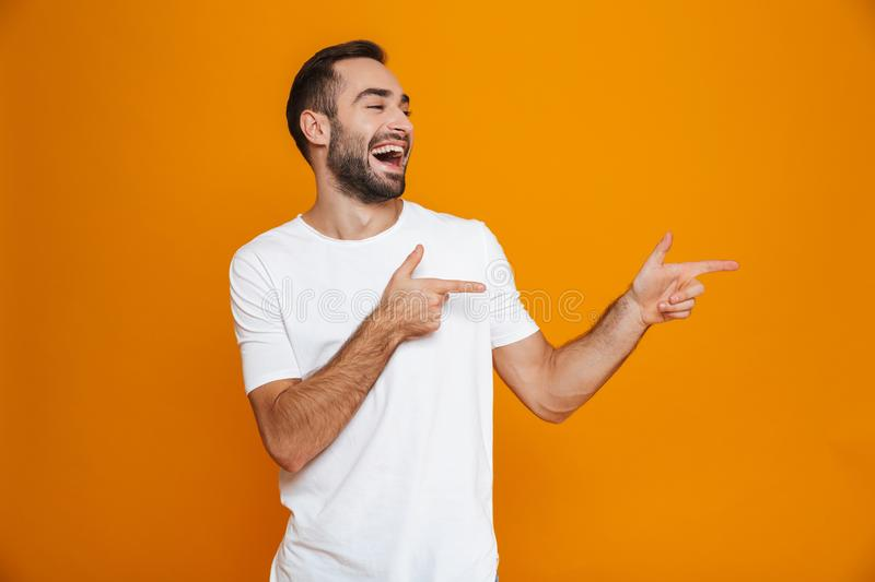 Image of good-looking guy 30s in t-shirt pointing fingers aside while standing, isolated over yellow background royalty free stock photography