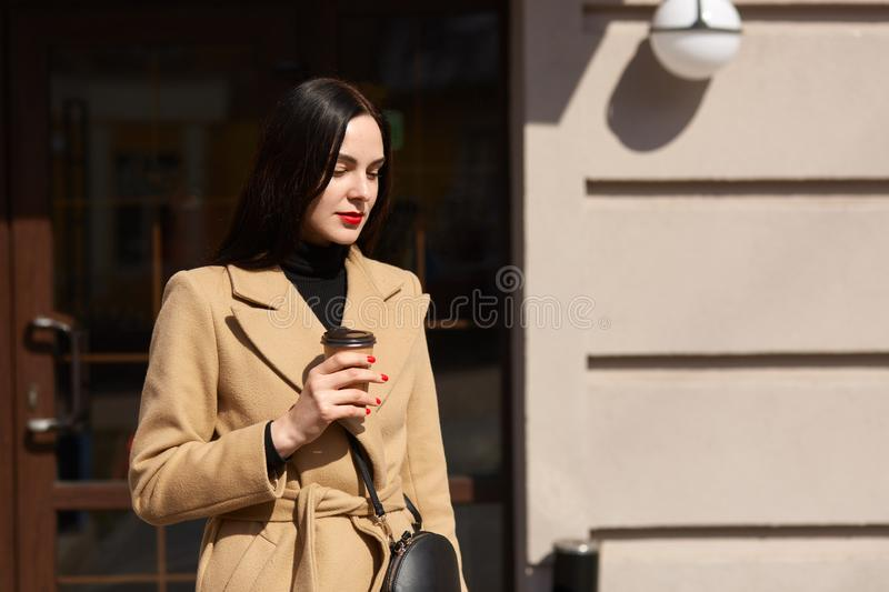 Image of gorgeous brunette woman with long hair, wearing coat and black handbag, has bright red manicure, holding takeaway coffee stock photo