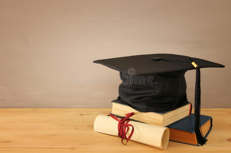 Image of graduation black hat over old books next to graduation on wooden desk. Education and back to school concept. stock photo
