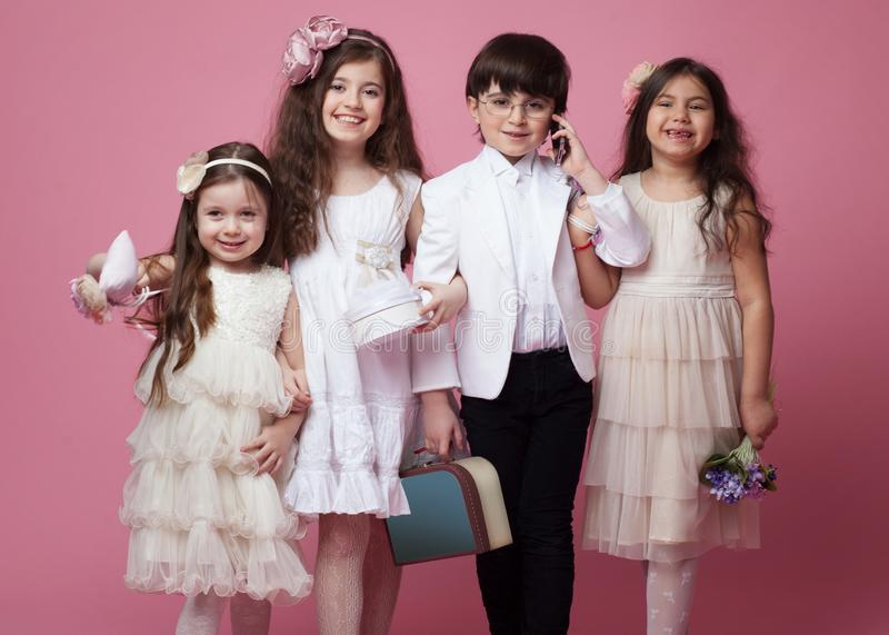 Frontal portrait of a group of happy children dressed in beautiful classic clothing, isolated on pink background. royalty free stock photo