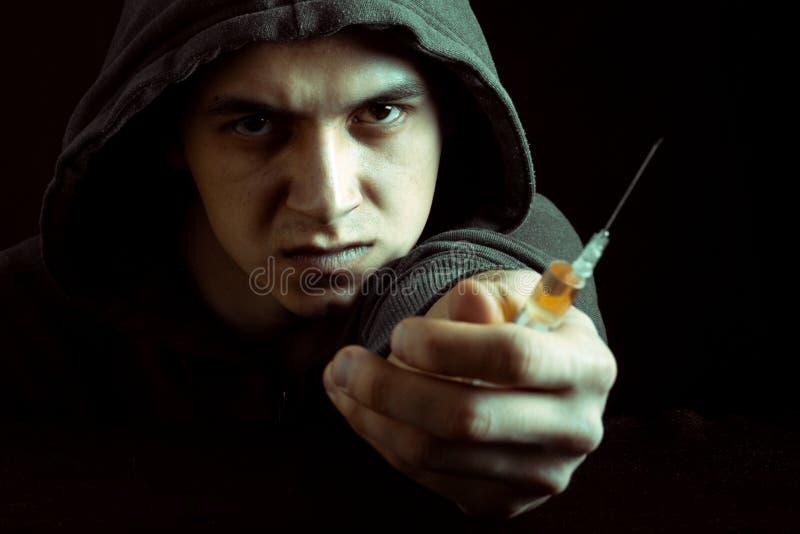Image grunge d'un toxicomane déprimé regardant une seringue et des drogues photographie stock libre de droits
